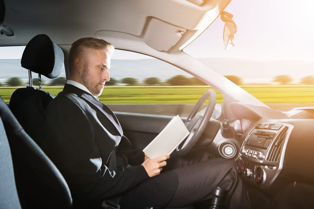 Man reading book while driving car